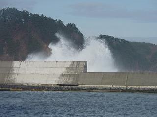 海は大荒れ。防波堤を超える波シブキ。